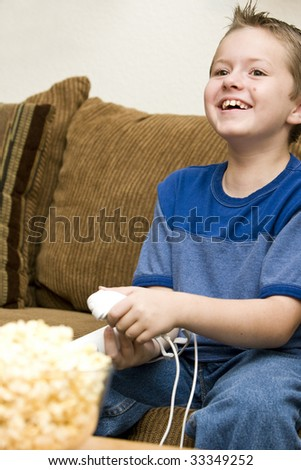 Young boy having fun playing video games at home - stock photo