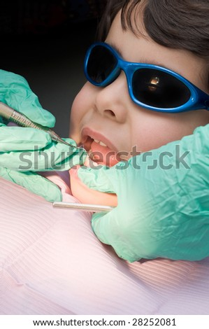 Young boy having his teeth cleaned at the dentist, doctor holding dental pick - stock photo