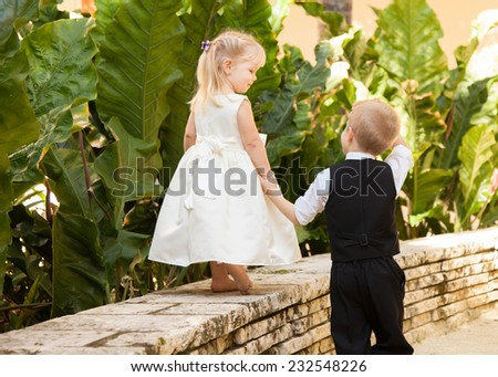 Young boy helping girl walk on a wall - stock photo