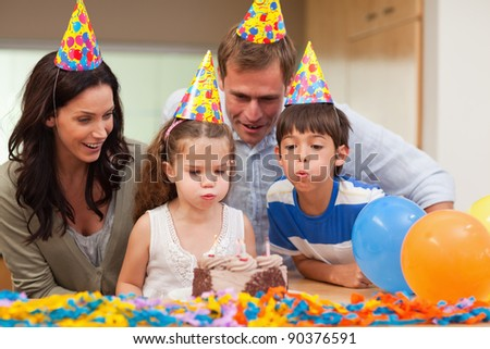 Young boy helping his little sister to blow out the candles on her birthday cake - stock photo