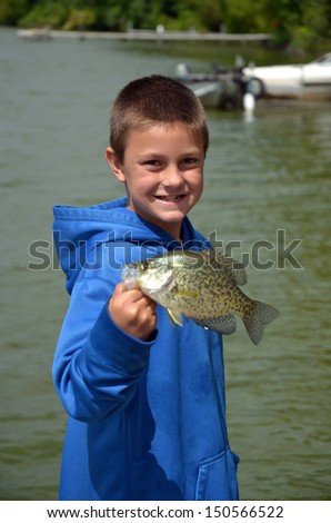 young boy holding a big crappie - stock photo