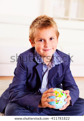 Young boy holding a globe in his hands. - stock photo