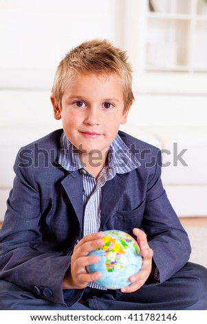 Young boy holding a globe in his hands.