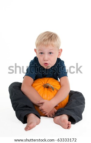 Young boy holding a pumpkin among his legs.