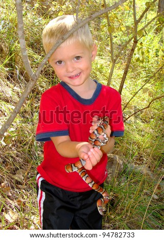 Young boy holding a snake in the forest, Red Milk Snake, Lampropeltis triangulum syspila