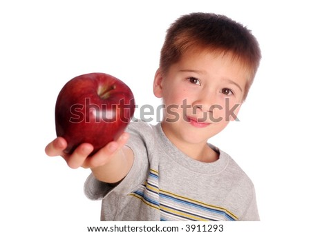 Young Boy Holding an Apple out to give his Teacher.  Focus in on the Boy. - stock photo