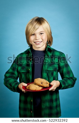 Young boy holding chocolate chip cookies isolated on blue background