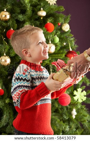 Young Boy Holding Christmas Present In Front Of Christmas Tree - stock photo