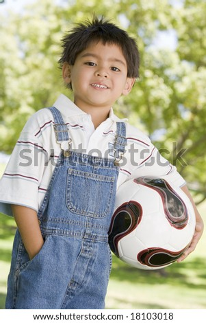 young boy holding football - stock photo