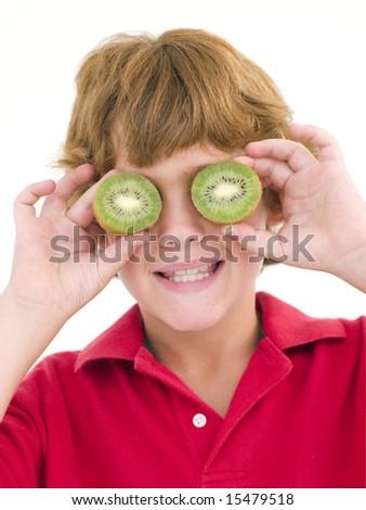 Young boy holding kiwi halves over eyes smiling - stock photo