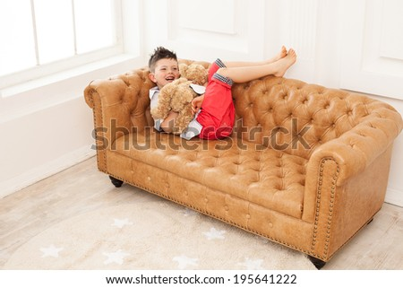 Young boy holding toy and laughing while lying down on sofa at home - stock photo