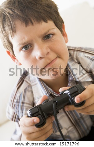 Young boy holding video game controller looking confused - stock photo