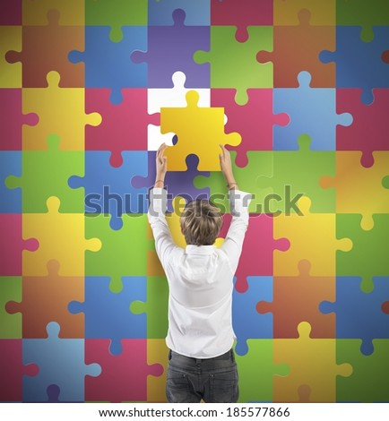 Young boy holds the missing piece of the puzzle - stock photo
