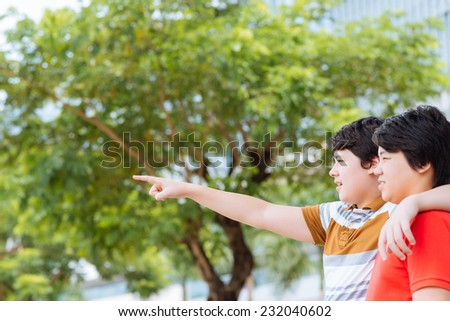 Young boy hugging his brother and pointing away - stock photo
