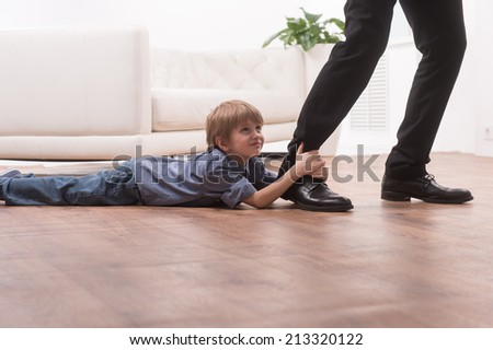Young boy hugging his father's leg. cute boy holding man and lying on floor - stock photo