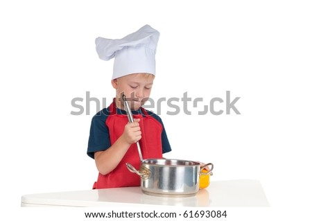 Young boy in a chef costume preparing food - stock photo