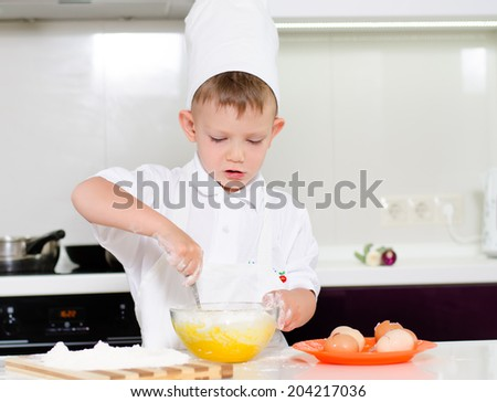 Young boy in a chefs uniform and toque baking whipping eggs in a mixing bowl as he bakes a cake in the kitchen - stock photo
