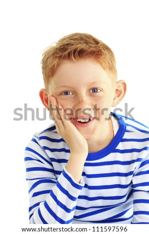 Young boy in a striped shirt smiles at the camera. Hand on his cheek. Vertical shot. Isolated on white. - stock photo