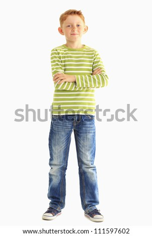 Young boy in a striped shirt smiles at the camera with crossed arms. Vertical shot. Isolated on white. - stock photo