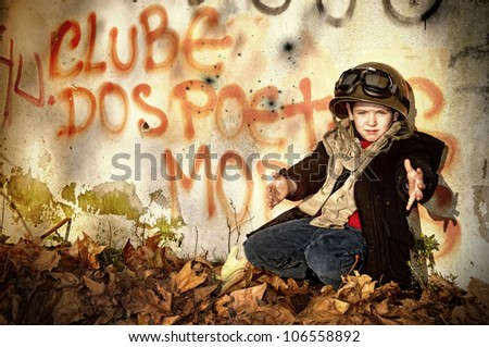 Young boy in a war zone crying for help - stock photo