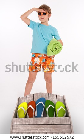 Young boy in beach wear and a group of colorful flip-flops - stock photo