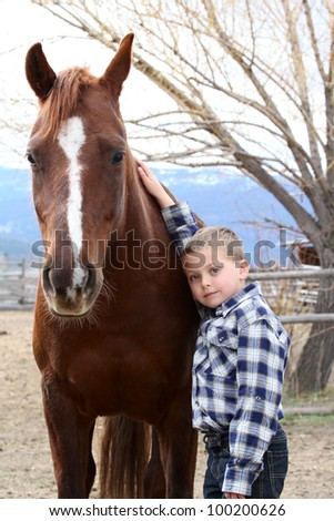 Young boy in blue leaning against his horse - stock photo