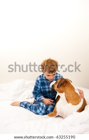 Young Boy in Blue Pajamas Talking to His Dog on Bed with White Sheets - stock photo