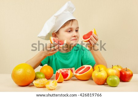 Young boy in chefs hat with two slices of grapefruit at the table with fruits - stock photo
