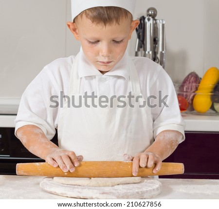 Young boy in chefs uniform rolling dough with a large wooden rolling pin as he prepares the base for a homemade Italian pizza - stock photo