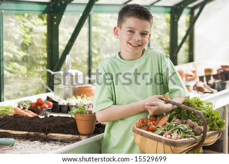 Young boy in greenhouse holding basket of vegetables smiling - stock photo