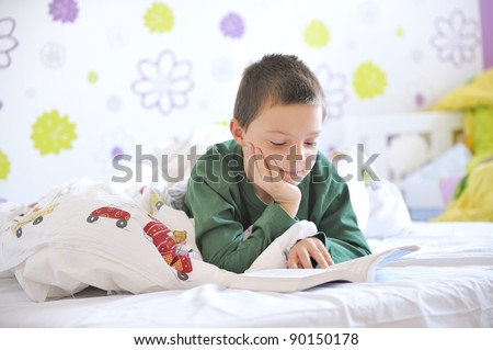 Young boy in his bed reading a book - stock photo