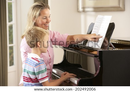 Young boy in lesson with piano teacher - stock photo