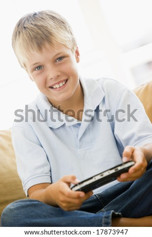 Young boy in living room with handheld video game smiling - stock photo