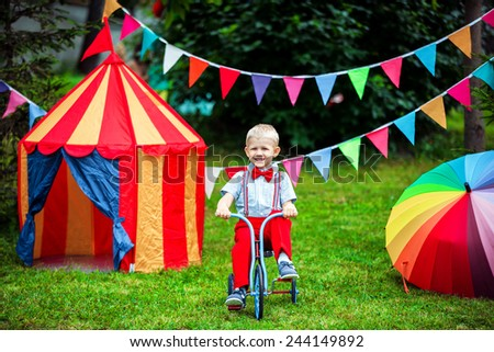 young boy in red pants and necktie outdoors on the bicycle - stock photo