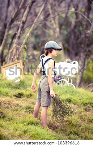 Young boy in retro clothing in woodland - stock photo