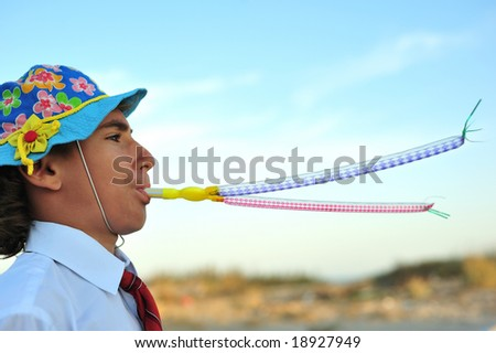 Young boy in shirt and tie blowing in blowers - stock photo