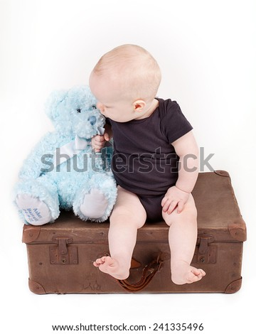 Young Boy in sitting on Vintage Suitcase with Teddy
