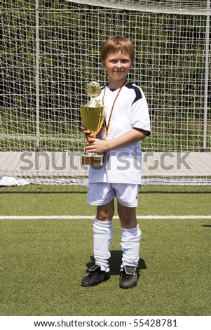young boy in soccer dress presents proud the cup which was won by his soccer team in a tournament - stock photo