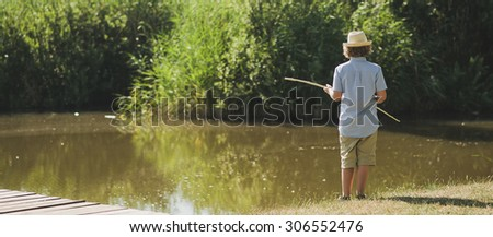 Young boy in straw hat and blue shirt playing with fishing rod like reed cane on the lakeside pier