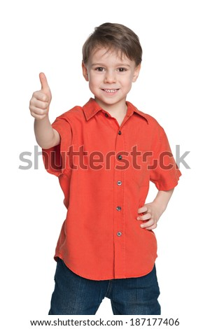 Young boy in the red shirt holds his thumb up on the white background - stock photo