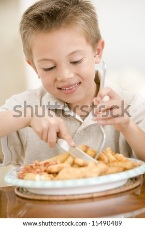 Young boy indoors eating fish and chips smiling - stock photo
