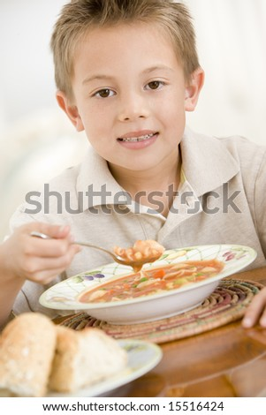 Young boy indoors eating soup - stock photo