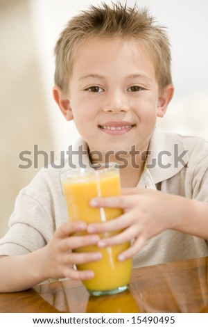 Young boy indoors with orange juice smiling - stock photo