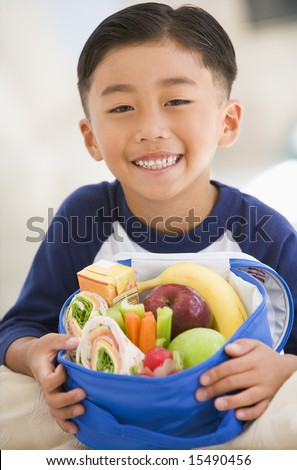 Young boy indoors with packed lunch smiling - stock photo