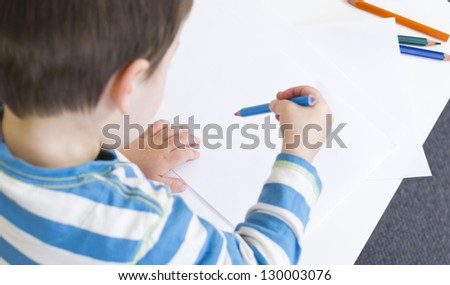 Young boy is about to draw with a blue pencil - stock photo