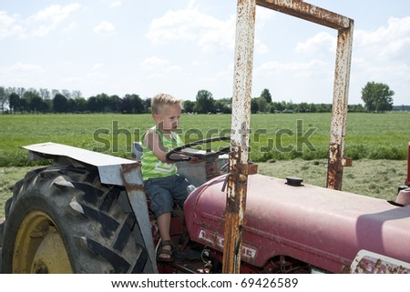 Young boy is driving a farm vehicle in the open.