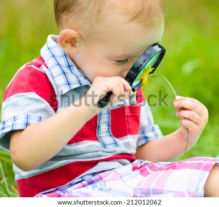 Young boy is looking at flower through magnifier, outdoor shoot - stock photo