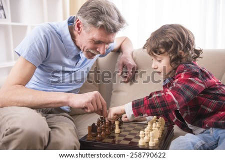 Young boy is playing chess with his grandfather at home. - stock photo