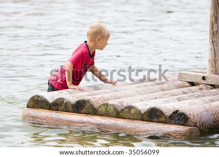 Young boy is pushing his raft in the water - stock photo