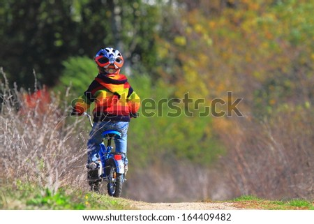 Young boy is riding his bike on dirt road - stock photo